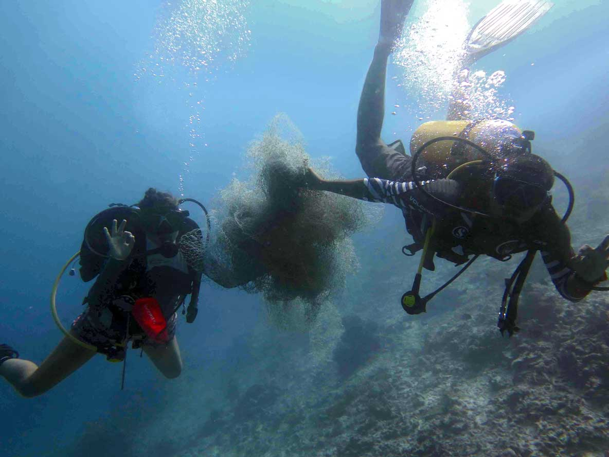 Divers swimming with ghost net Maldives