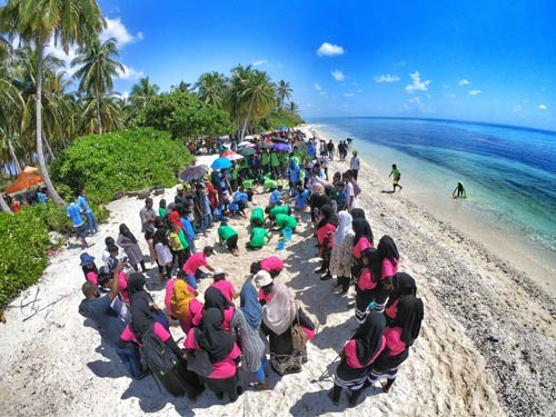 Group of people cleaning a beach in Maldives. Photo