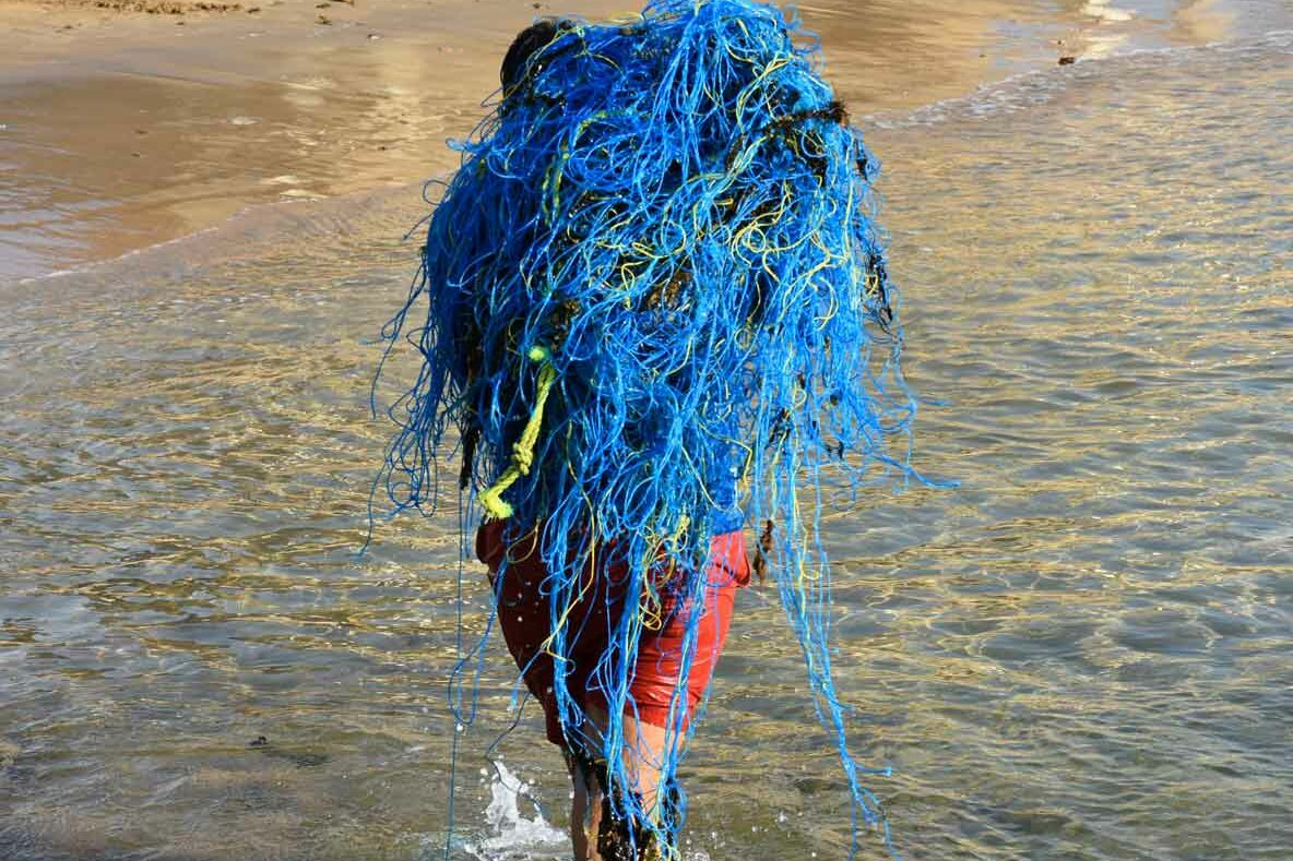 ORP staff carrying ghost net out of the ocean