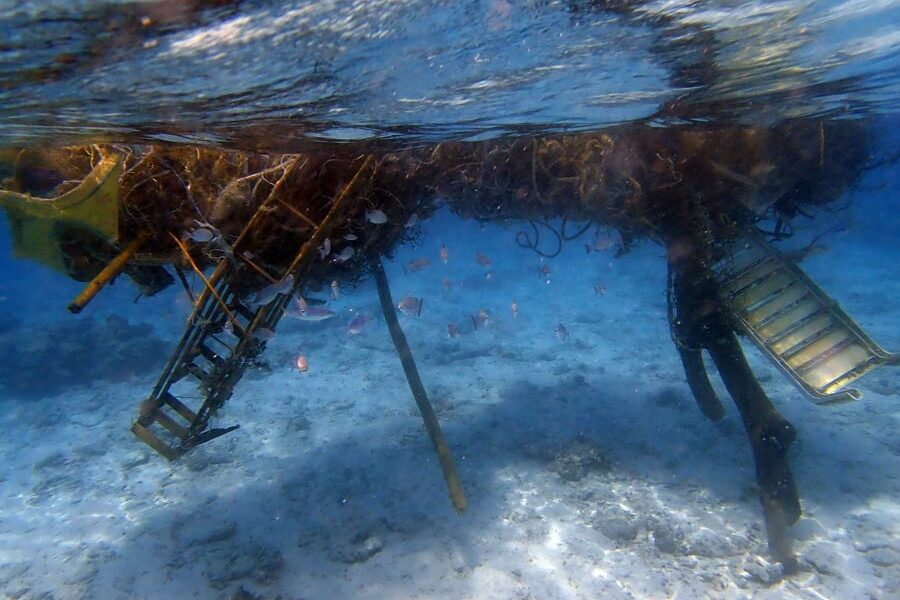 Monster ghost net with a deck chair, stairs and a tree trunk entangled, North Male Atoll, Maldives