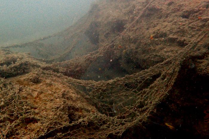 Ghost gear on rocks in the sea. Image.